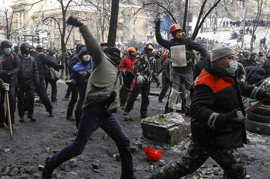 Pro-European integration protesters throw stones towards riot police in Kiev, on Thursday, January 23, 2014.Ukraine's opposition agreed on Thursday, to observe an eight-hour truce in clashes with security forces after five days of deadly fighti