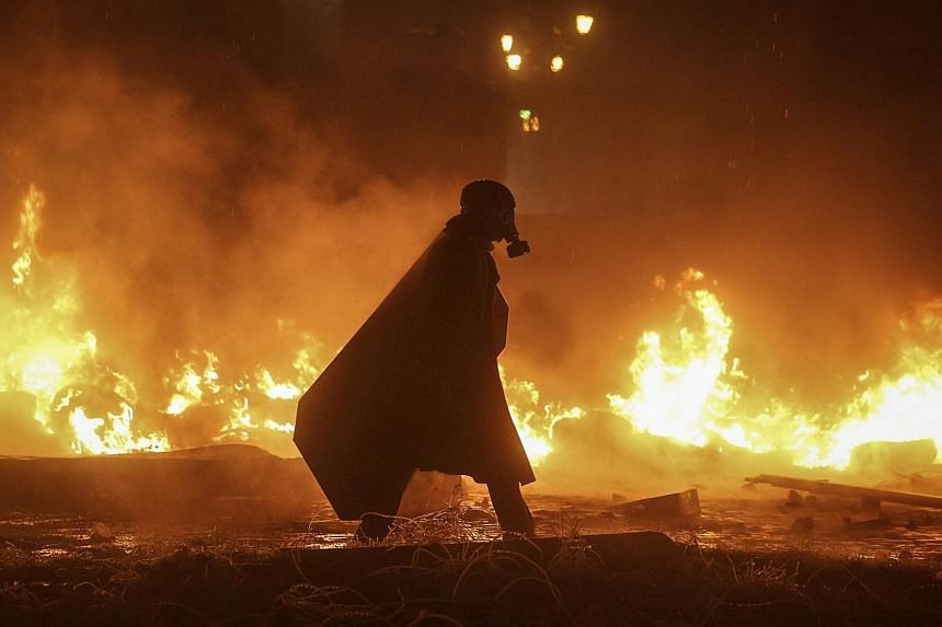 A pro-European integration protester walks among burning tyres at the site of clashes with riot police in Kiev on Jan 22, 2014. -- PHOTO: REUTERS
