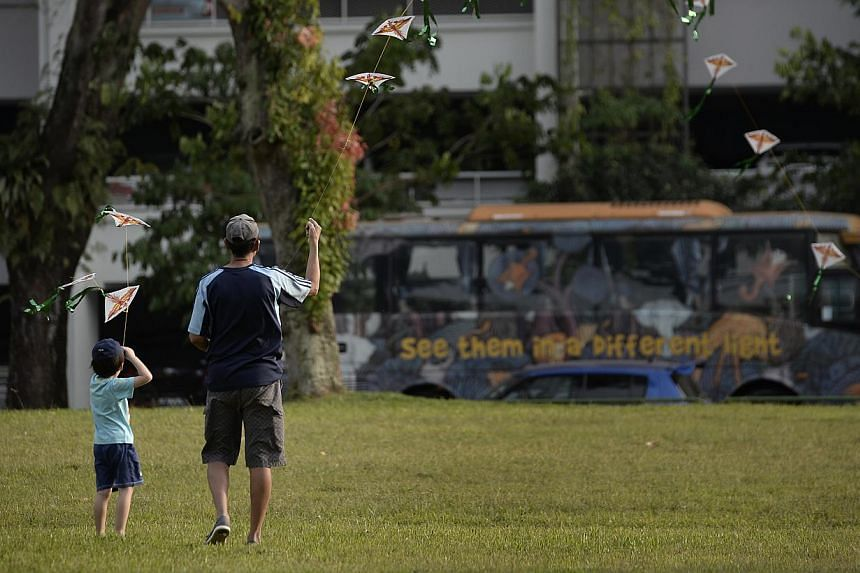 A boy and his grandfather flying kites in Toa Payoh on Wednesday. The past week has seen wind gusts of up to 72kmh. -- ST PHOTO: MUGILAN RAJASEGERAN