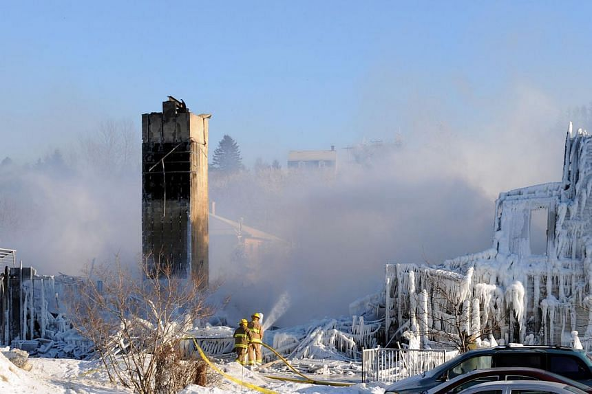 Smoke rises from the burnt remains of a retirement home in L'Isle-Verte on Jan 23, 2014. Canadian firefighters searched the ashes of a Quebec retirement home Thursday after it burned nearly to the ground on a bleak midwinter night, leaving more