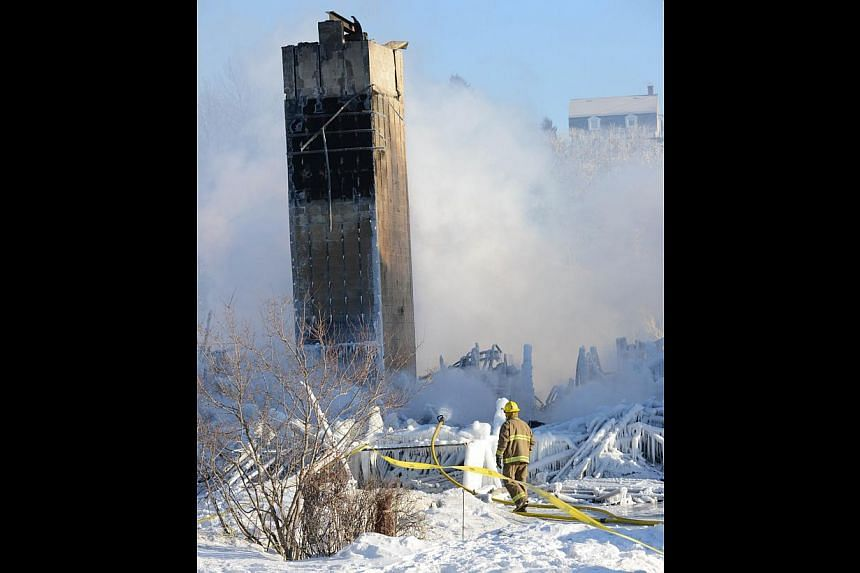 Smoke rises from the burnt remains of a retirement home in L'Isle-Verte on Jan 23, 2014. -- PHOTO: AFP