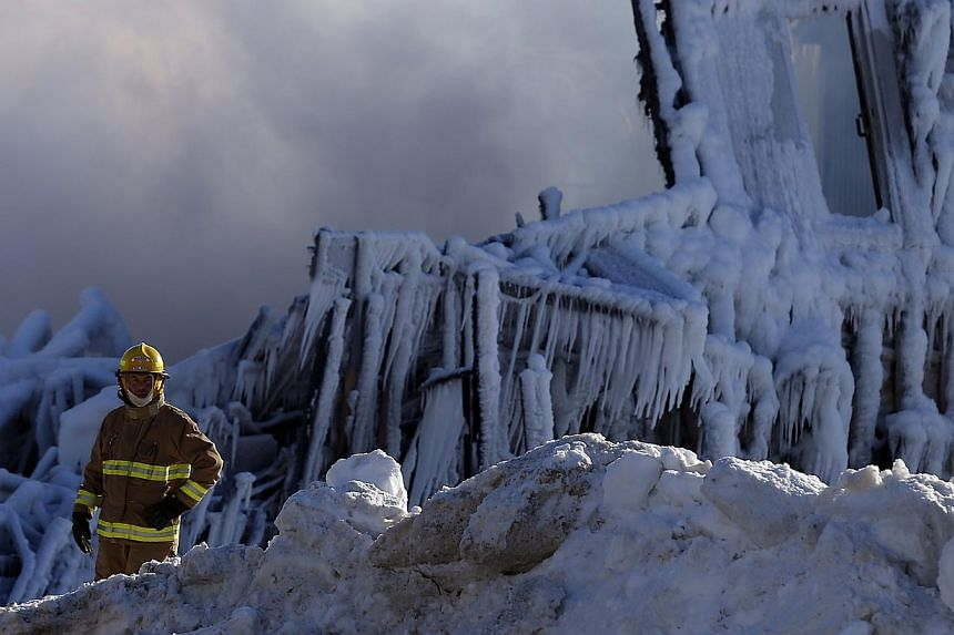 A firefighter looks on at the seniors residence Residence du Havre after a fire in L'Isle Verte, Quebec, on Jan 23, 2014. -- PHOTO: REUTERS