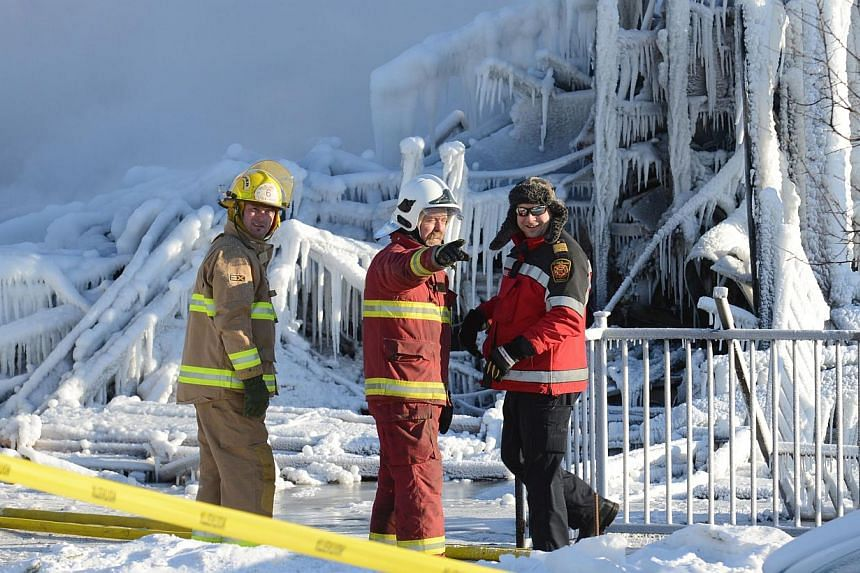 Canadian firefighters inspect the burnt remains of a retirement home in L'Isle-Verte on Jan 23, 2014. -- PHOTO: AFP