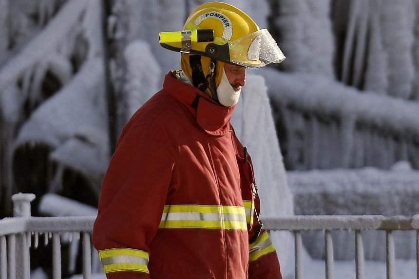 A firefighter walks past the Residence du Havre after a fire in L'Isle Verte, Quebec, on Jan 23, 2014. -- PHOTO: REUTERS