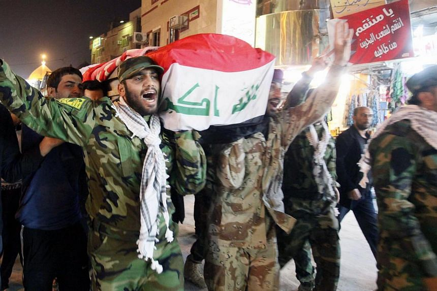 Mourners carry the coffin of a fighter from the Iraqi Shi'ite the Badr Organization, who was killed in clashes with the Free Syrian Army, during a funeral in Najaf, 160 km (99 miles) south of Baghdad, on Jan 23, 2014. Nearly 1,400 people have be