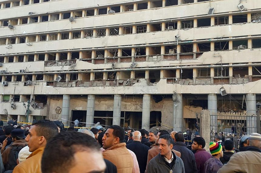 Police officers and people gather in front of the destroyed Islamic Museum building, after a bomb blast occurred at the police headquarters nearby, in downtown Cairo, on Jan 24, 2014. A car bomb struck Cairo police headquarters on Friday, killing at