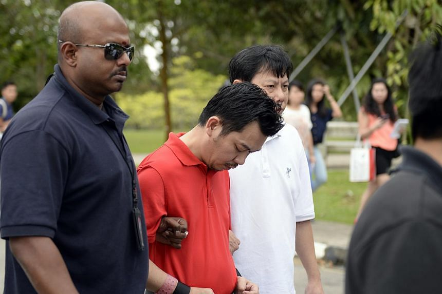 Lee Sze Yong (in red), one of the accused involved in the Sheng Siong kidnapping case, is brought back to Sembawang Park for police investigations on Jan 20, 2013.The two men, including Lee, who were allegedly involved in the Sheng Siong kidnap
