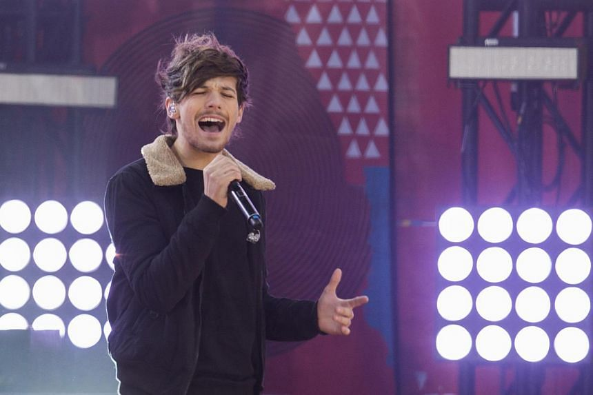 One Direction singer Louis Tomlinson of the band One Direction performs on ABC's Good Morning America inside Central Park in New York, on Nov 26, 2013. Louis Tomlinson will trade in his microphone for football boots next month when he makes his debut