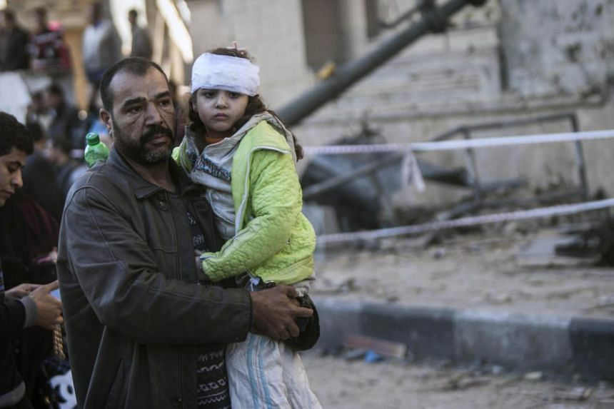 An Egyptian man carries an injured girl at the site of a car bomb explosion outside the Cairo police headquarters on Jan 24, 2014, which killed several people, police and health ministry officials said. -- PHOTO: AFP