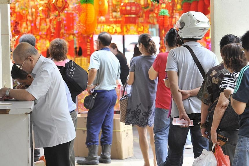 The Toto queue at Blk 102 Yishun Ave 5 on Friday, Jan 24, 2014. The winning numbers of the Toto Reunion draw, which came with a jackpot prize of $5 million, have been announced.-- ST PHOTO:MATTHIAS HO