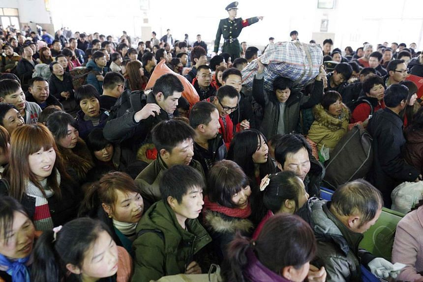 A paramilitary policeman tries to control passengers at a railway station in Hangzhou, Zhejiang province, on Jan 24, 2014.China is gearing up for the peak travel period of the world's largest annual human migration, as the Spring Festival natio