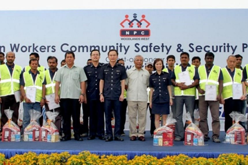 Mr Hawazi Daipi, Senior Parliamentary Secretary for the Ministry of Manpower and Education, with the Foreign Worker Ambassadors. -- PHOTO: SINGAPORE POLICE FORCE