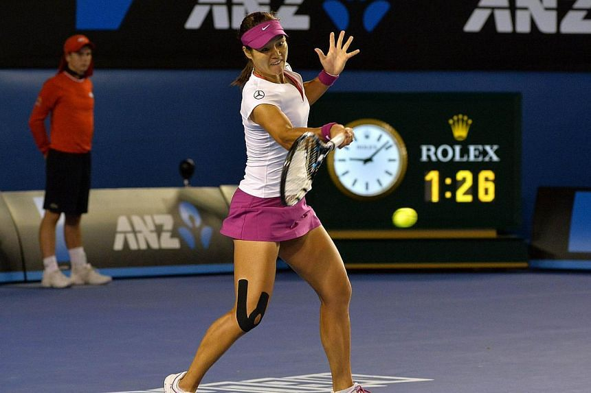 Li Na of China hits a return against Dominika Cibulkova of Slovakia during the women's singles final on day 13 of the 2014 Australian Open tennis tournament in Melbourne, on Jan 25, 2014. -- PHOTO: AFP
