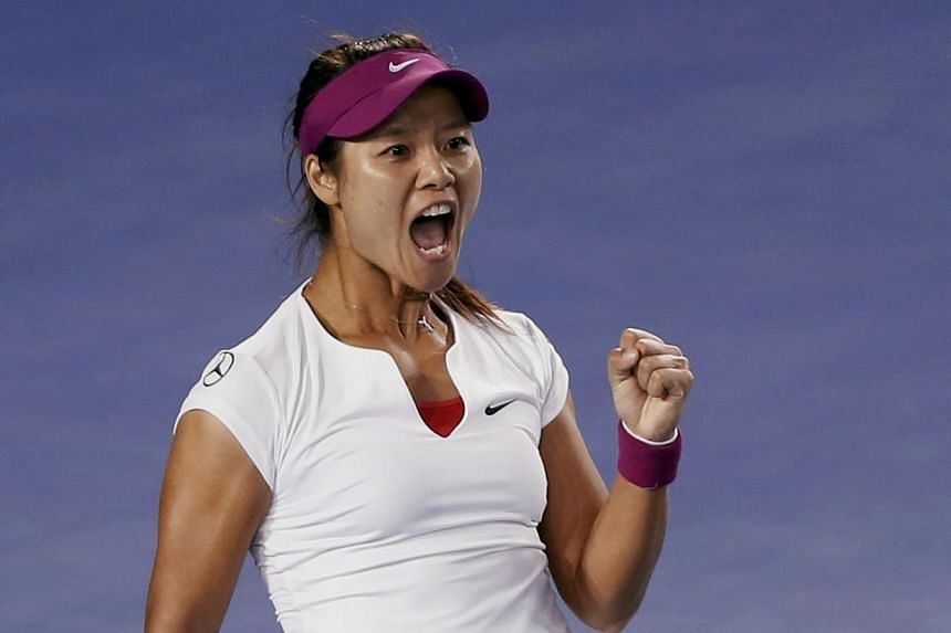 Li Na of China celebrates winning the first set during her women's singles final match against Dominika Cibulkova of Slovakia at the Australian Open 2014 tennis tournament in Melbourne, on Jan 25, 2014. -- PHOTO: AFP
