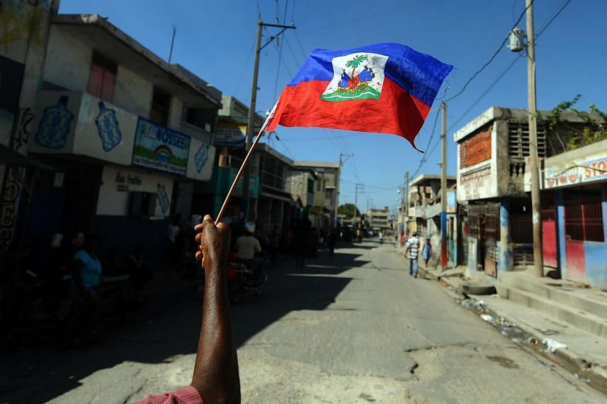 A man holds a Haitian flag as he takes part in a protest demanding that Haitian President Michel Martelly step down in Port-au-Prince on Jan 13, 2014. Opposition parties in Haiti launched talks on Friday with President Michel Martelly and parlia