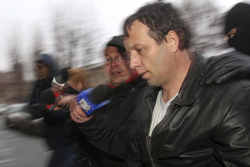 """Marcel Lazar Lehel, 40, is escorted by masked policemen in Bucharest, after being arrested in Arad, 550 km (337 miles) west of Bucharest on Jan 22, 2014.Romanian hacker Lehel, known as """"Guccifer"""", appealed against his arrest on Friday but the c"""