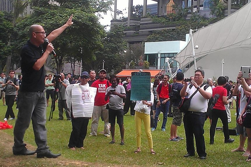 Mr Gilbert Goh (left), founder of Movement for a Better Singapore, speaking to protesters.-- ST PHOTO: PRISCILLA GOY