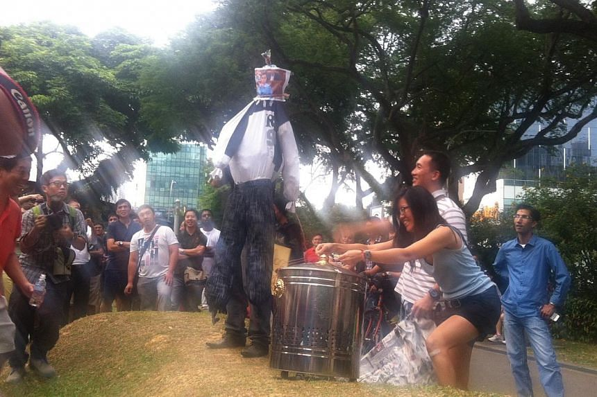 An effigy of Transport Minister Lui Tuck Yew is held up by protest organiser Gilbert Goh. -- ST PHOTO: THAM YUEN-C