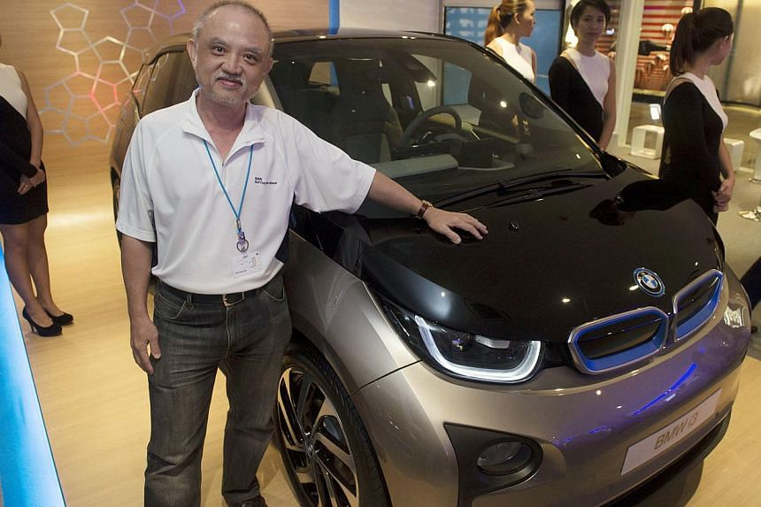 Businessman Yap Pow Look standing next to a BMW's new electric car. -- ST PHOTO: NURIA LING