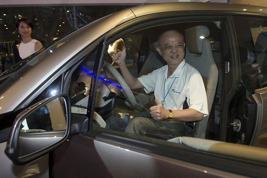 Businessman Yap Pow Look sitting in a BMW's new electric car. -- ST PHOTO: NURIA LING