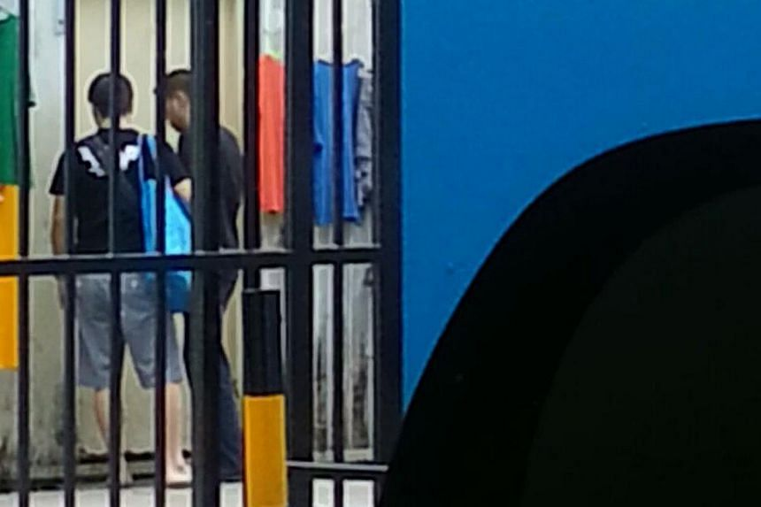 Two suspected peddlers leaving a store selling contraband cigarettes in Geylang. Both have since been arrested.