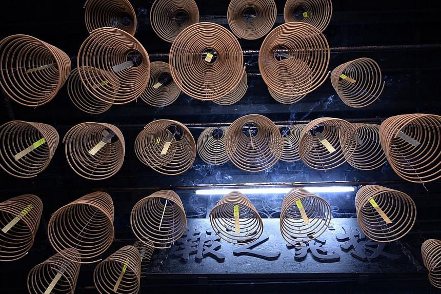 Coils of incense hanging from the temple's ceiling bearing the wishes of devotees on yellow strips.