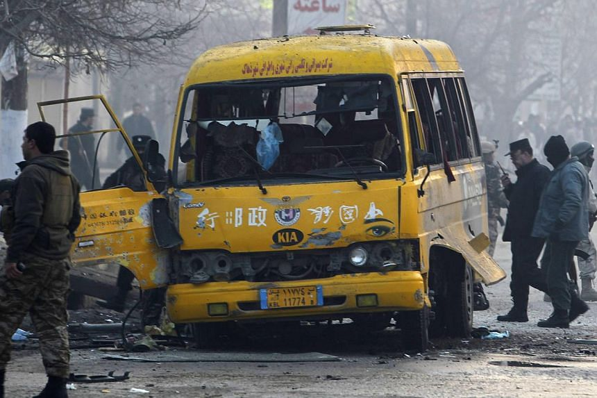 Afghan policemen inspecting the wreckage of a bus hit by a suicide attack in Kabul on Jan 26, 2014. A Taleban suicide bomber killed at least four people in Kabul on Sunday when he targeted a Ministry of Defence bus, officials said, confirming three p