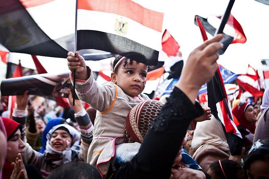 Egyptians wave the national flag in Cairo's Tahrir Square during a rally marking the anniversary of the 2011 Arab Spring uprising on Jan 25, 2014. -- PHOTO: AFP