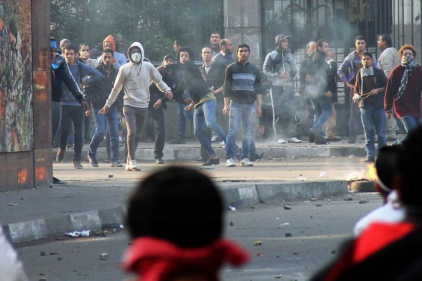 Muslim Brotherhood supporters (background) clash with supporters of the Egyptian government in Cairo on Jan 25, 2014. -- PHOTO: AFP