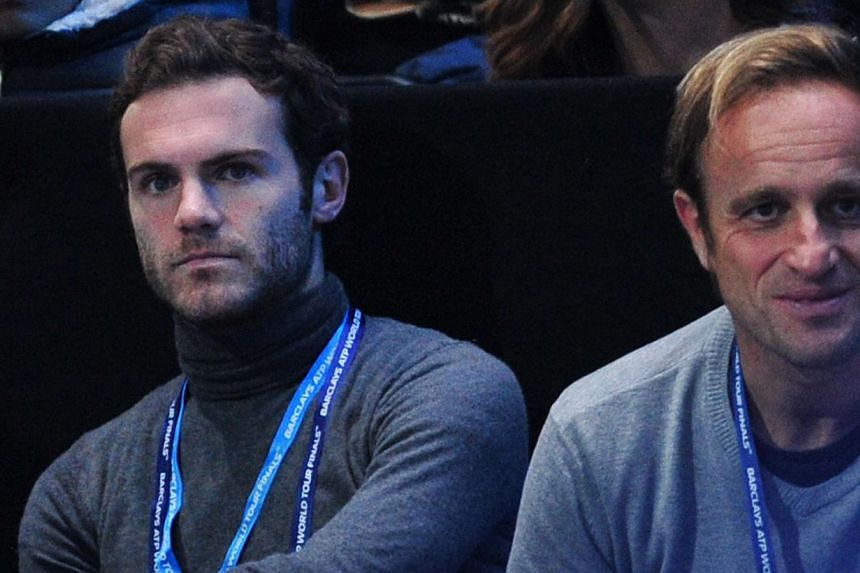 Chelsea's Spanish midfielder Juan Mata (left) watches Switzerland's Roger Federer play against Spain's Rafael Nadal in their singles semi-final match on the seventh day of the ATP World Tour Finals tennis tournament in London on Nov 10, 2013. -- FILE