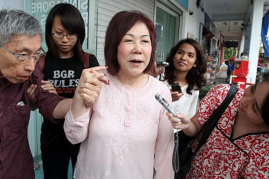 Opposition politician Lina Chiam (centre) speaking to reporters as she guides her husband, Chiam See Tong (left) out of the Singapore People's Party (SPP) headquarters on Jan 5, 2014. Mr and Mrs Chiam have retained their leadership positions in the S