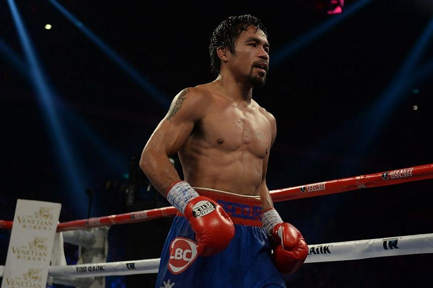 Manny Pacquiao of the Philippines returns to his corner after a round during his welterweight boxing bout against Brandon Rios of the US in Macau on Nov 24, 2013. Pacquiao will return to the ring for a re-match and the chance of revenge against Ameri