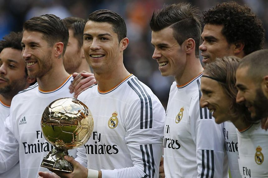 Real Madrid's Cristiano Ronaldo (centre) holds his Ballon d'Or (Golden Ball) trophy with his teammates after winning the Fifa World Player of the Year 2013 award, before their Spanish first division soccer match against Granada at the Santiago Bernab