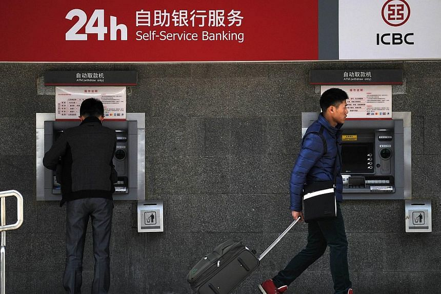 """A man (right) walks past an ATM machine with his baggage at the entrance of a bank in Beijing on Jan 25, 2014. A shockwave is looming in China's multi-trillion dollar """"shadow banking"""" system, with an unprecedented default only days away on a US$500 m"""
