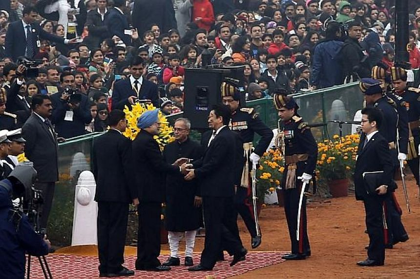 In this handout photograph released by the Ministry of Defence, on Jan 26, 2014, Indian Prime Minister Manmohan Singh (third left) greets Japanese Prime Minister Shinzo Abe (fourth right) while Indian President Pranab Mukherjee (centre) looks on duri