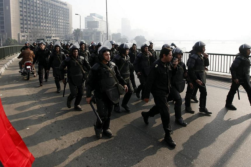 Riot police are seen on October bridge during clashes with anti-government protesters and members of the Muslim Brotherhood, near Tahrir Square in downtown Cairo, on the third anniversary of Egypt's uprising, on Jan 25, 2014. -- PHOTO: REUTERS