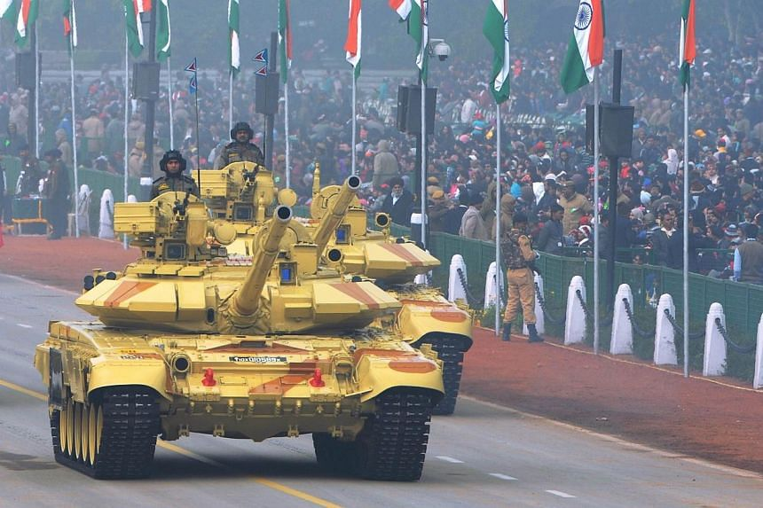 Indian Army tanks roll in formation past spectators during the Republic Day parade in New Delhi, on Jan 26, 2014. -- PHOTO: AFP