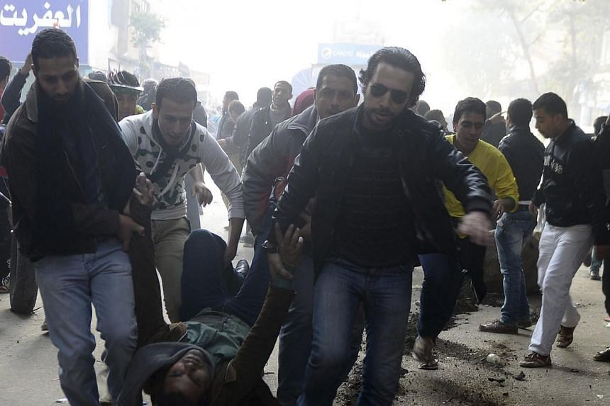 Supporters of the Muslim Brotherhood and ousted Egyptian President Mohamed Mursi carry an injured demonstrator who was shot during clashes in Cairo, on the third anniversary of Egypt's uprising, Jan 25, 2014. At least 49 people have been killed in 24