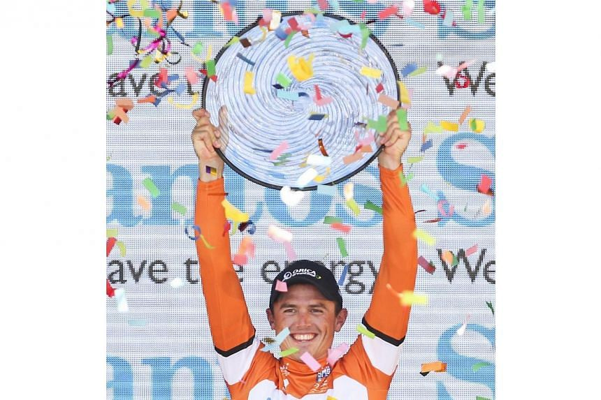 Simon Gerrans from Australia holds the trophy on the podium after winning the overall race after stage 6 of the 2014 Tour Down Under cycling race on Sunday, January 26, 2014. Gerrans stayed out of trouble in Sunday's final stage to finish ahead