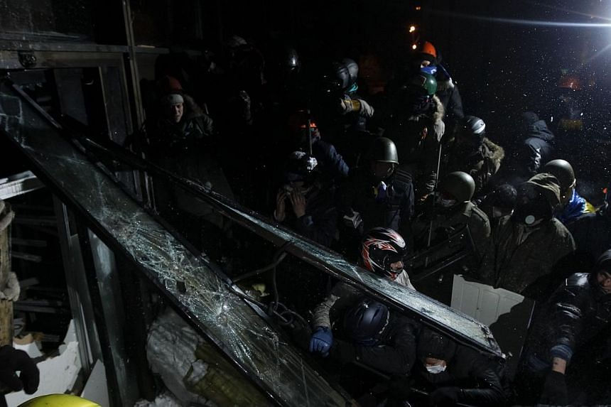 """Anti-government protesters try to enter the """"Ukrainian House"""" where the riot police are located during a rally in Kiev, on Jan 25, 2014. Protesters in the Ukrainian capital Kiev on Sunday, Jan 26, 2014, ousted special police forces from a flash"""