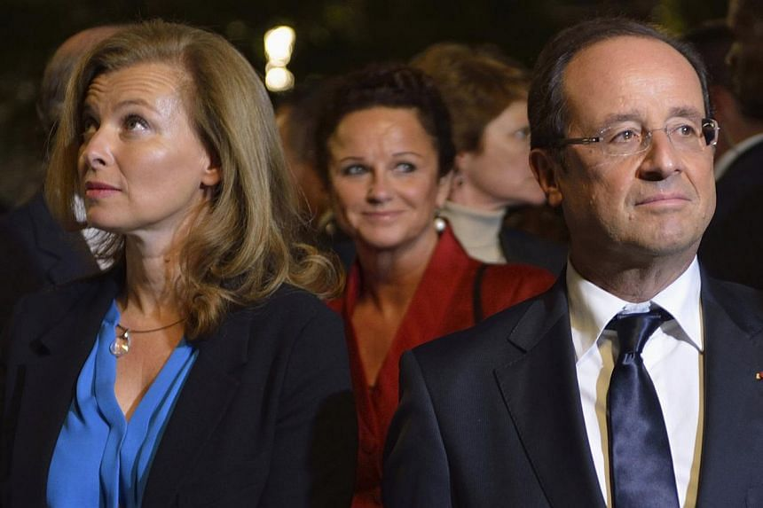 French President Francois Hollande and companion Valerie Trierweiler (left) visit the September 11 Memorial at Ground Zero, site of the Twin Towers that were destroyed on Sept 11, 2001, at the World Trade Center in New York on Sept 25, 2012. -- FILE