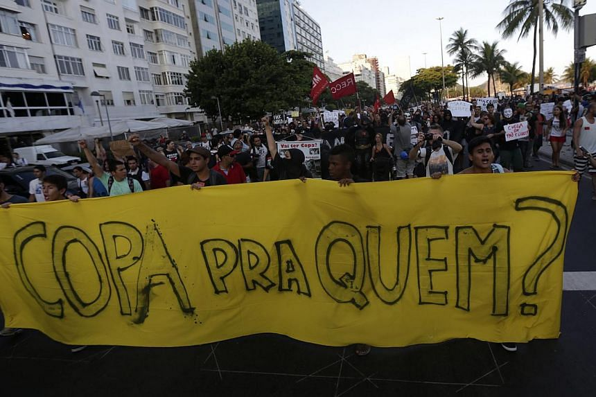 """Demonstrators march during a protest against the 2014 World Cup in Copacabana, Rio de Janeiro on Jan 25, 2014. The banner reads """"Cup for who?"""" -- PHOTO: REUTERS"""