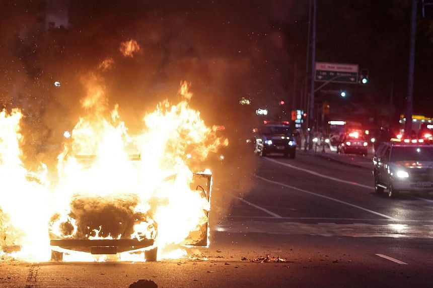 """A car burns in flames during the """"Nao Vai Ter Copa"""" (You are not going to have Cup) protest along Consolacao Street, in Sao Paulo, Brazil, on Jan 25, 2014. -- PHOTO: REUTERS"""