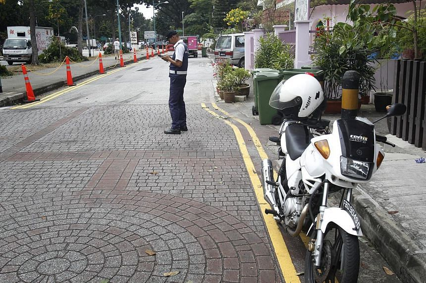 A traffic warden checking parking on Jalan Mas Puteh. Previously, residents clamped the wheels of illegally-parked vehicles there, but now the road has been converted to public land and wardens patrol the area regularly.