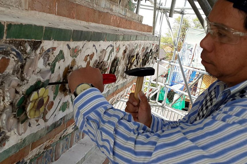 Mr Chitipat Chotirak at work, chipping away for long hours every day at the old lime around the ceramic relief works of the 17th century Wat Arun temple. -- ST PHOTO: NIRMAL GHOSH