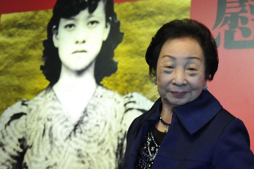 """In this archived photo, former Taiwanese """"comfort woman"""" Chen Lien Hua stands in front of a poster for Korean American artist Lee Chang-jin's """"Comfort Women Wanted"""" exhibition in Taipei on December 9, 2013. The exhibition, on display between December"""