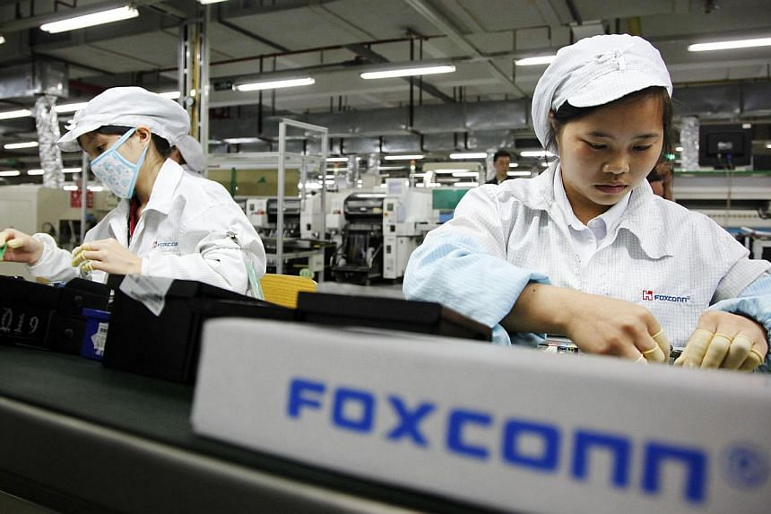 Employees work on the assembly line at Taiwanese manufacturer Foxconn's plant in Shenzhen, China. Beset by rising costs and labour unrest in China, Chairman Terry Gou told employees on Sunday that Foxconn is considering diversifying away from its man