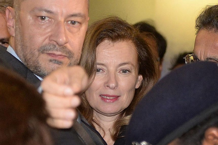 Ms Valerie Trierweiler (centre), the ex-partner of French President Francois Hollande, surrounded by security guards and officials, arrives at the international airport in Mumbai early on Jan 27, 2014. -- PHOTO: AFP