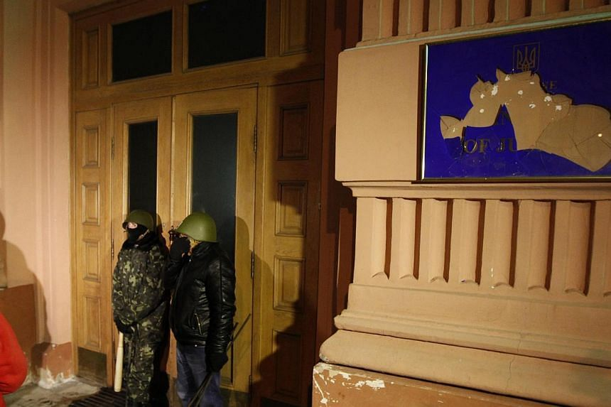 Anti-government protesters stand at the entrance of the Ministry of Justice in central Kiev, on Jan 27, 2014. Ukraine threatened to impose a state of emergency on Monday after demonstrators occupied the justice ministry and protests demanding the pre