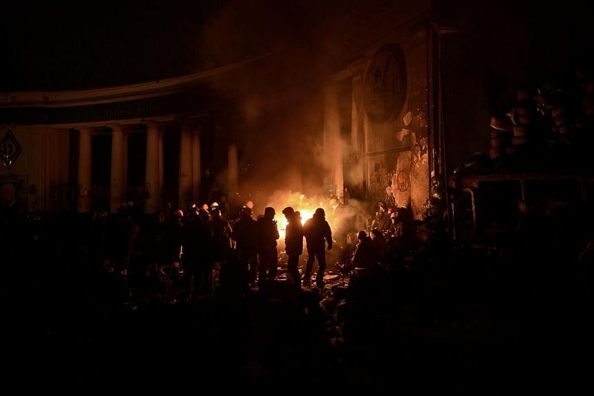 Anti-government protesters gather around a fire to get warm at a road block in Kiev on Jan 26, 2014.Ukrainian police on Sunday, Jan 26, 2014, dispersed thousands of protesters who had rallied in the south-eastern region of Zaporozhiya in a bid